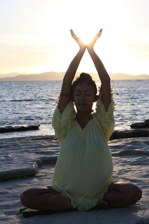 太陽の光を浴びながらヨガをする田中律子